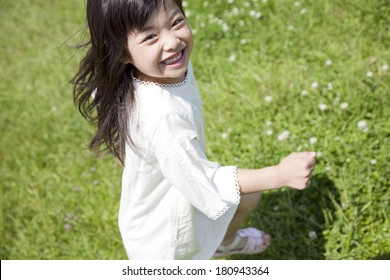 Japanese girl smiling and running in grass