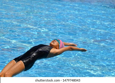 Japanese girl is swimming the backstroke in the pool