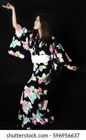 Japanese girl in traditional Japanese kimono on black background. Isolated photo.