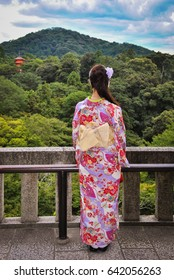 Japanese girl in traditional kimono outfit looking at the temple