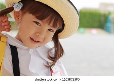 Japanese girl in uniform in kindergarten yard in summer (3 years old)