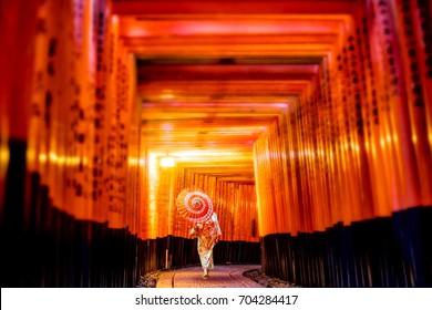 Japanese girl in Yukata with red umbrella at Fushimi Inari Shrine in Kyoto, Japan
