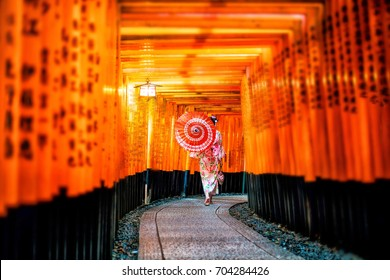 Japanese girl in Yukata with red umbrella at Fushimi Inari Shrine in Kyoto, Japan