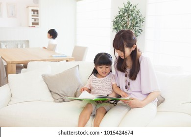 Japanese girls get to read a book on the couch to mom
