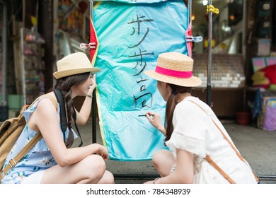 "japanese girls writing the wishes on the sky lanterns in chinese on Shifen Old Street section of Pingxi District. Translation on sky lanterns text "" hopes of success in career"""
