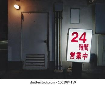 """Japanese glowing neon billboard by night,  it's written """"24h opened"""" in Japanese."""