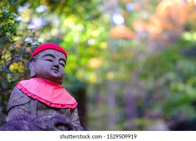 Japanese god statue with red apron in mitakidera temple garden, Hiroshima