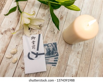 "Japanese goreizen envelope with script saying ""before the spirit of the deceased"". With a candle. Given with money inside and presented to the family."