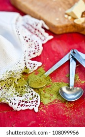 Japanese green tea in measurement spoon with white chocolate on red wooden surface