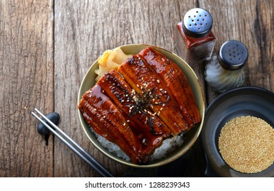 Japanese grilled eel with sweet sauce on rice cup or unagi kabayaki in Japanese menu name photo with indoor lighting.