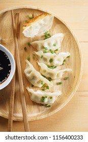 Japanese gyoza, fried dumplings, with soy sauce on wooden plate