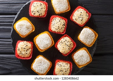 Japanese healthy rice dessert mochi daifuku with anko and sesame seeds close-up on the table. horizontal top view from above