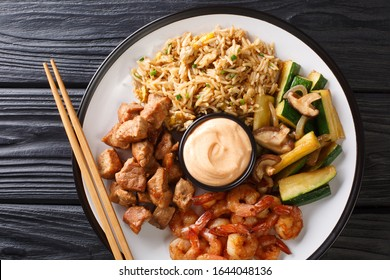 Japanese Hibachi recipe of rice, shrimp, steak and vegetables served with sauce closeup in a plate on a table. Horizontal top view from above