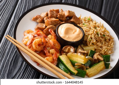 Japanese Hibachi recipe of rice, shrimp, steak and vegetables served with sauce closeup in a plate on a table. horizontal