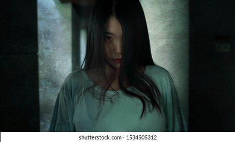 Japanese horror movie style portrait of young strange Asian girl at night in dark solitary hotel corridor looking weird and shady in fear and scary Halloween tribute
