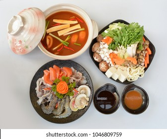 Japanese Hot and Sour Seafood hot pot with udon and vegetables boiled in water, kaisen kimuchi nabe on black pottery plate, isolated on white background
