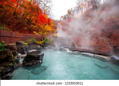Japanese Hot Springs Onsen Natural Bath Surrounded by red-yellow leaves. In fall leaves fall in Yamagata. Japan.