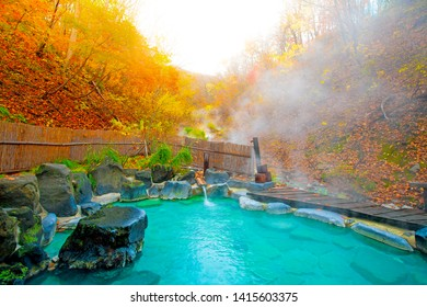 Japanese Hot Springs Onsen Natural Bath Surrounded by red-yellow leaves. In fall leaves fall in Japan.Waterfall among many foliage, In the fall leaves Leaf color change.