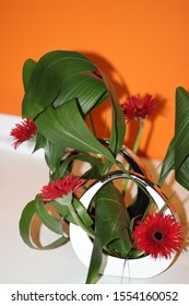 Japanese ikebana of red flowers and green leaves