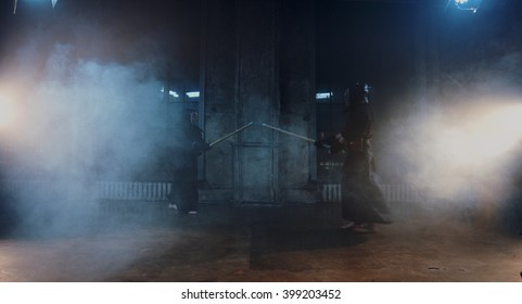 Japanese kendo fighters with bamboo swords competing in dark industrial building in the fog.