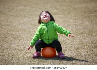 Japanese kid playing with an orange ball in a park in Tokyo, Japan.