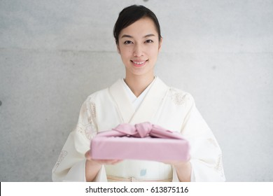 Japanese kimono woman holding a gift against concrete wall