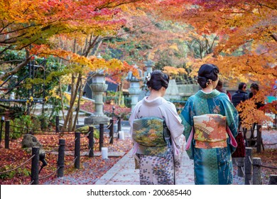 Japanese ladies in kimono enjoy autumn leaves