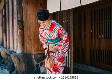 Japanese lady bowing in front of her house with beautiful kimono. traditional lifestyle in jp. attractive woman with colorful kimono clothing in summer.