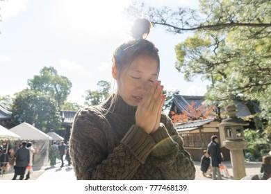 Japanese lady worshiping at a shrine