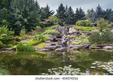 Japanese lake in Grand Rapids, Michigan, United States Calm water of a lake with a waterfall in a japanese garden, surrounded by trees and plants. Meijer Garden, Grand Rapids, Michigan, United States.