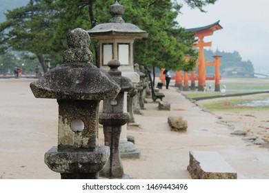 Japanese lanterns and pines trees satnd in rows in front of the famous Itsukushima Floating Torii gate on Miyajima Island near Hiroshima, Japan on a misty and rainy day.