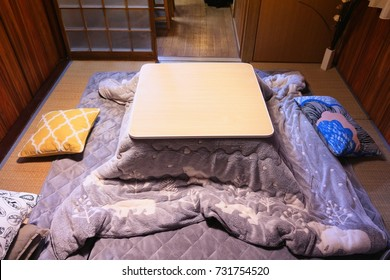 Japanese living room with kotatsu - table with heating and attached blanket for winter warmth.
