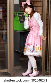 Japanese lolita dressed in pink lolita cosplay is calling in a phone public booth