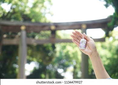 Japanese lucky charm. A hand holding omamori or A Japanese lucky charm to wish good luck in love relationship.