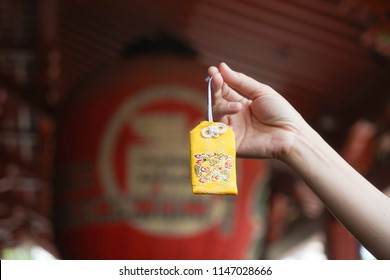 Japanese lucky charm. A hand holding a yellow omamori or A Japanese lucky charm to grant a wish fulfillment