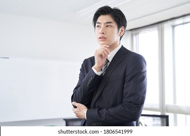 Japanese male businessman in a conference room thinking