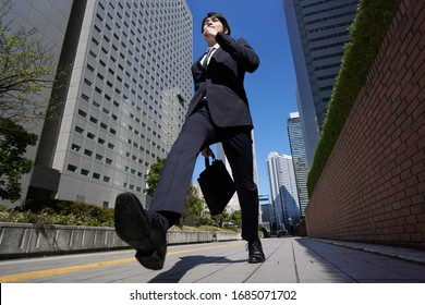 A Japanese male businessman walks briskly through an office district.