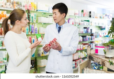 Japanese male specialist is helping female client choose medicine in pharmacy.