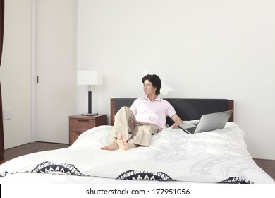 Japanese man looking out with a laptop in a hand on the bed