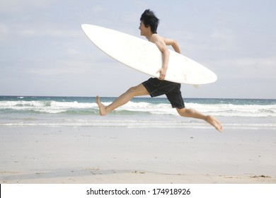 Japanese Man running with surfboard into the sea