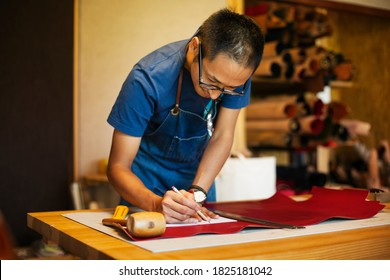 Japanese man wearing blue apron working in a leather shop.