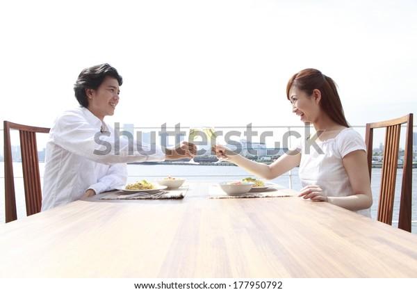 テラスでトーストを飲む日本人男性と日本人女性