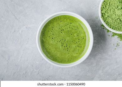 Japanese matcha green tea latte in white bowl on gray stone background. Top view