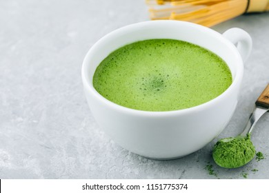 Japanese matcha green tea latte in white cup on gray stone background.