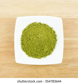 The Japanese matcha green tea powder on the mini white dish on wooden board.