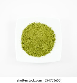 The Japanese matcha green tea powder on the mini white dish.