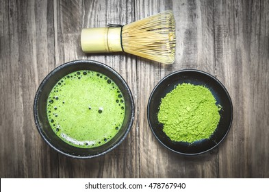 Japanese matcha green tea and matcha green tea powder at homemade clay bowl with bamboo whisk on wooden table with vignette tone