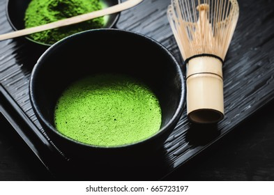 Japanese matcha green tea and matcha green tea powder at homemade clay bowl with bamboo whisk on black wooden table with vignette tone