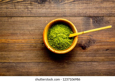 Japanese matcha tea tradition. Matcha accesories near matcha powder in bowl on dark wooden background top view copy space