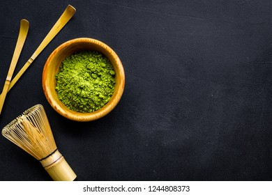 Japanese matcha tea tradition. Matcha accesories, whisk near matcha powder in bowl on black background top view copy space